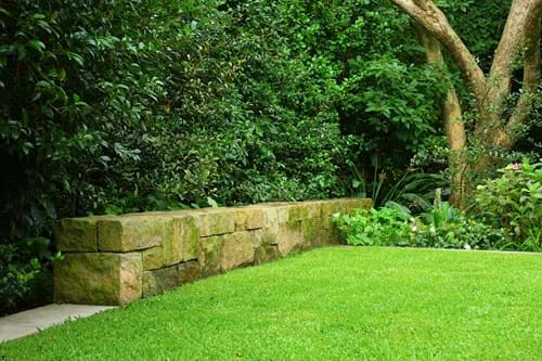 Sandstone block blade wall as a garden feature with mixed planting for green screening